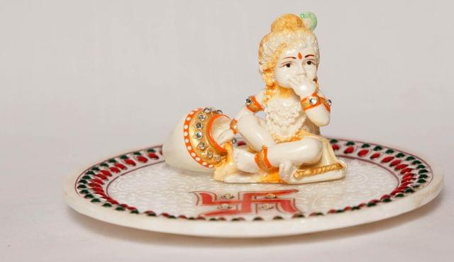 Young lord Krishna with Laddu