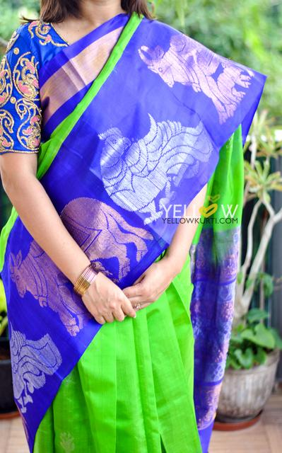 Bright green Kuppadam handloom silk saree with blue border intricately woven with silver and gold zari figures
