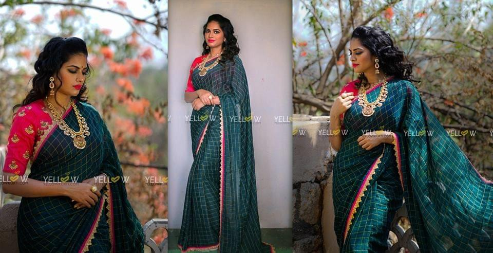 Bottle green georgette saree with Zari checks and golden borders.