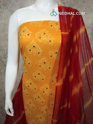 Printed Yellow Cotton Unstitched salwar material with foil mirror work on front side , red cotton bottom, Printed red chiffon dupatta with tapings.