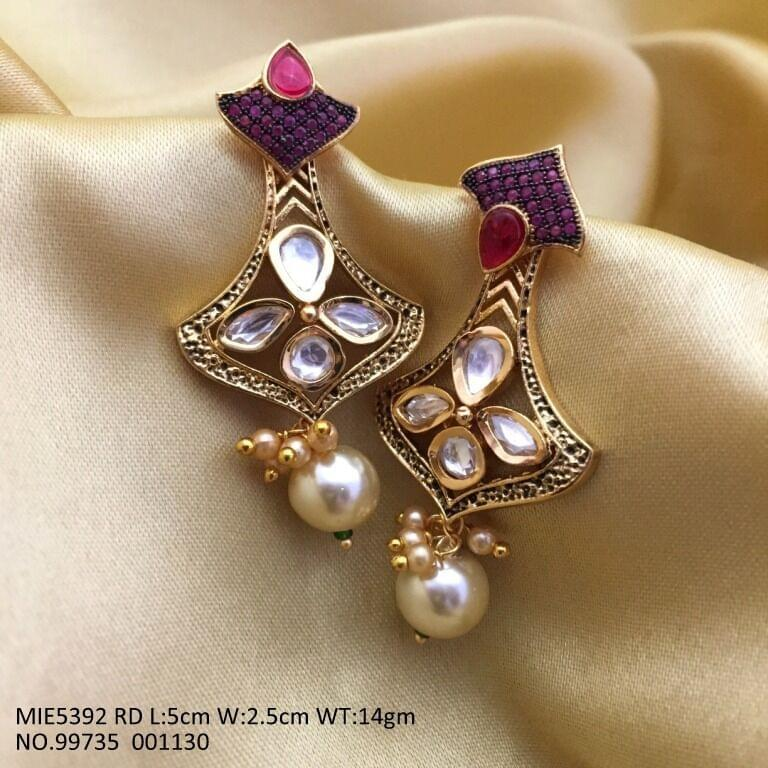Jhumki /Dangler studded with semi precious stones and a pearl is dangling at the end. Its base metal is brass
